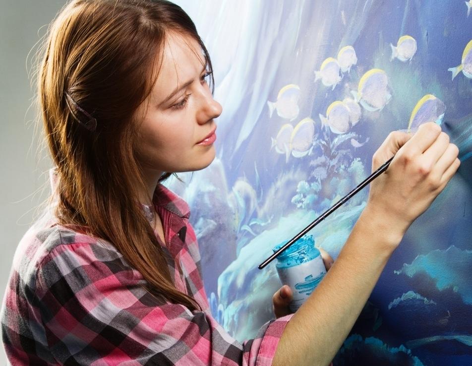 Femme en train de faire du graphique & design sur un mur bleu lumineux elle démontre la créativité de nos prestataires en graphique & design vin